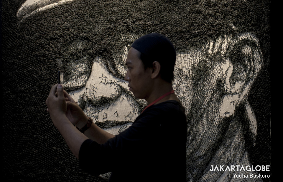 A man takes a selfie in front of a Iwan Jusufs painting at National Cultural Week in Istora, Central Jakarta on Tuesday (08/10). (JG Photo/Yudha Baskoro)