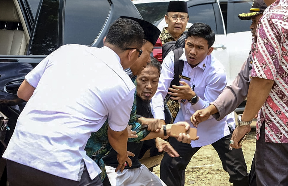 Aides rush to assist Chief Security Minister Wiranto, second from left, during the attack. (Antara Photo/Police handout)
