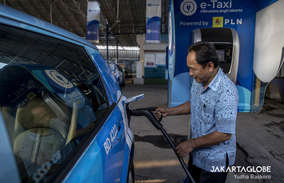 A driver charges a BYD e6 electric taxi at the Blue Bird Group's headquarters in Mampang, South Jakarta, on Friday. (JG Photo/Yudha Baskoro)