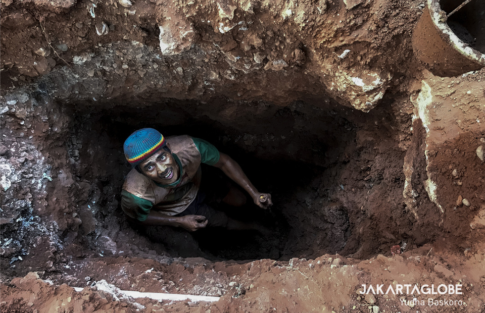 A worker digs a hole for the construction of an aqueduct in front of Lotte Shopping Avenue in Kuningan, South Jakarta, on Friday. (JG Photo/Yudha Baskoro)