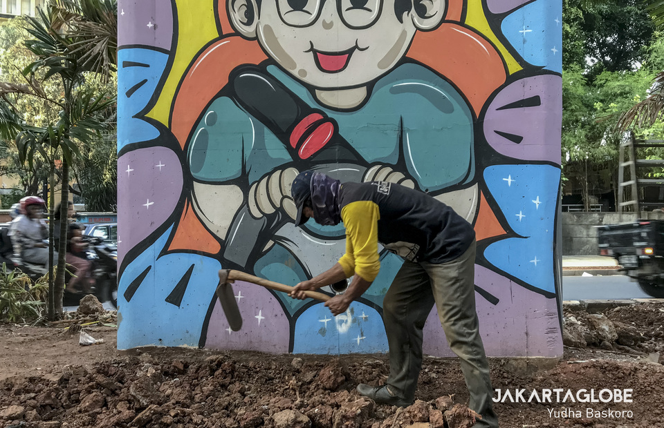 A worker uses a hoe to clear an area for a green open space under the Casablanca overpass. (JG Photo/Yudha Baskoro)