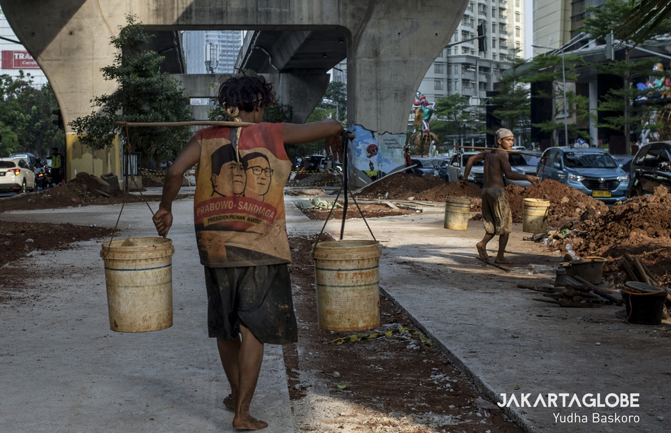 Workers carry water used to soften the soil and make it easier to dig. (JG Photo/Yudha Baskoro)