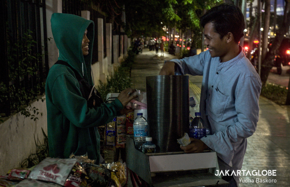 Elquze, 24 (left) ask Mukhlis Riyadi, 24 (right) to give some ice to him at Sarinah shopping complex in Central Jakarta on Wednesday (16/10). Communal life and 'esprit de corps' soul make it easy for them to survive in the capital city with little income. (JG Photo/Yudha Baskoro)