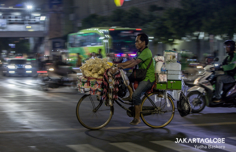 Working late into the night - a starling rides his bike near Sarinah intersection in Central Jakarta on Wednesday (16/10). (JG Photo/Yudha Baskoro)
