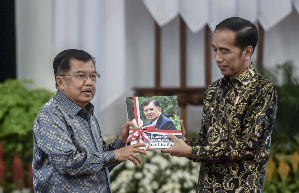 President Joko Widodo gives incumbency memory book to Vice President Jusuf Kalla in working cabinet gathering at State Palace in Central Jakarta on Friday (18/10). Vice President Jusuf Kalla has been Vice President of Indonesia since 2014. (Antara Photo/Akbar Nugroho Gumay)