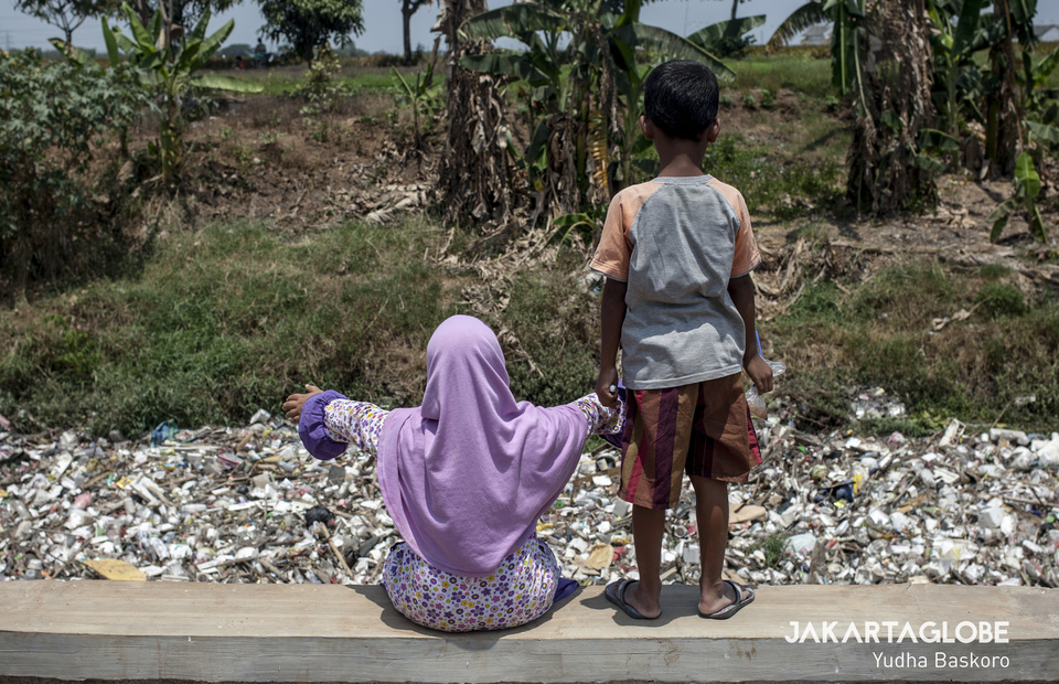 Two children play near the Kali Jambe River in Bekasi, West Java on Wednesday (30/10). (JG Photo/Yudha Baskoro)
