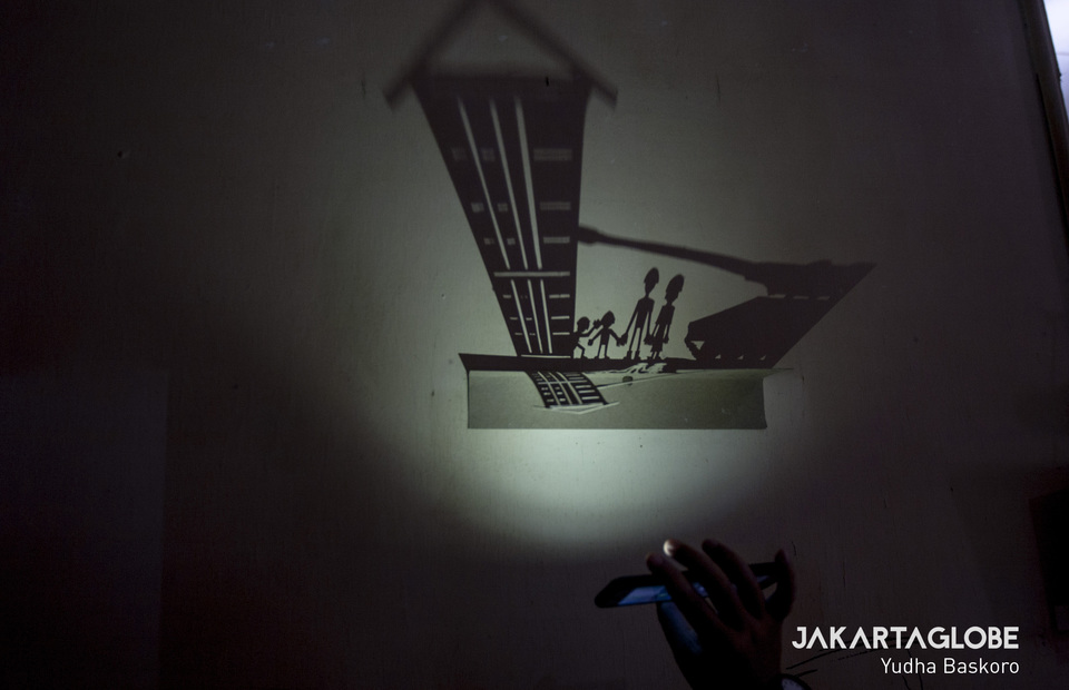 A visitors turn on a flashlight under an artwork at 2019 Biennale Jogja XV in Ketandan 17, Yogyakarta on Friday (01/11). (JG Photo/Yudha Baskoro)