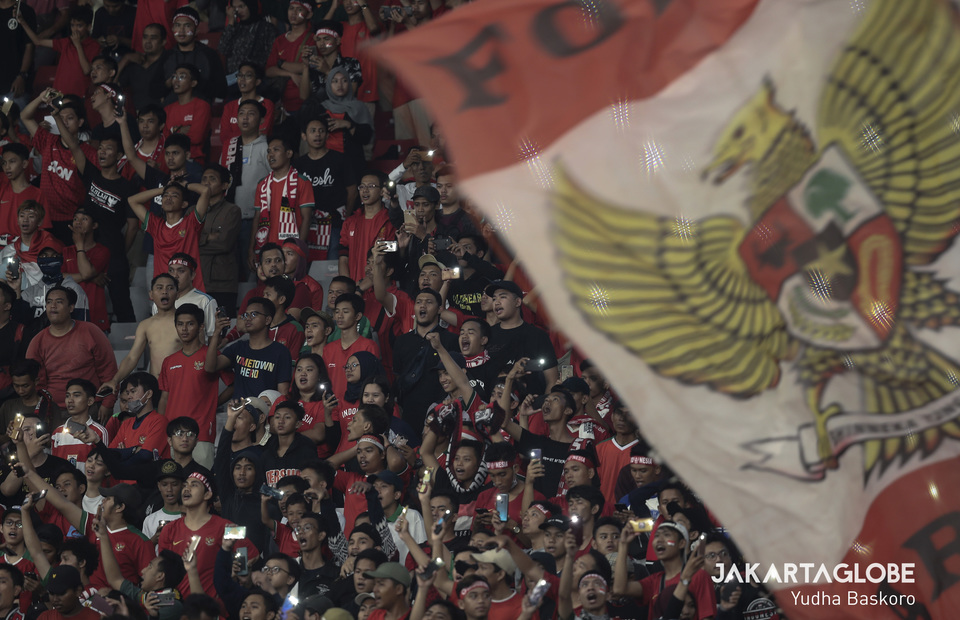 Indonesian supporters sing Tanah Airku and light up their flash light during 2020 AFC U-19 Championship qualifying round againts North Korea at Gelora Bung Karno Stadium, Central Jakarta on Sunday (10/11). (JG Photo/Yudha Baskoro)