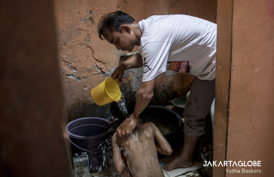 Oding bathed his daughter in his home at Cengkareng, West Jakarta on Monday (11/11) He spent his time for family during the training break. (JG Photo/Yudha Baskoro)