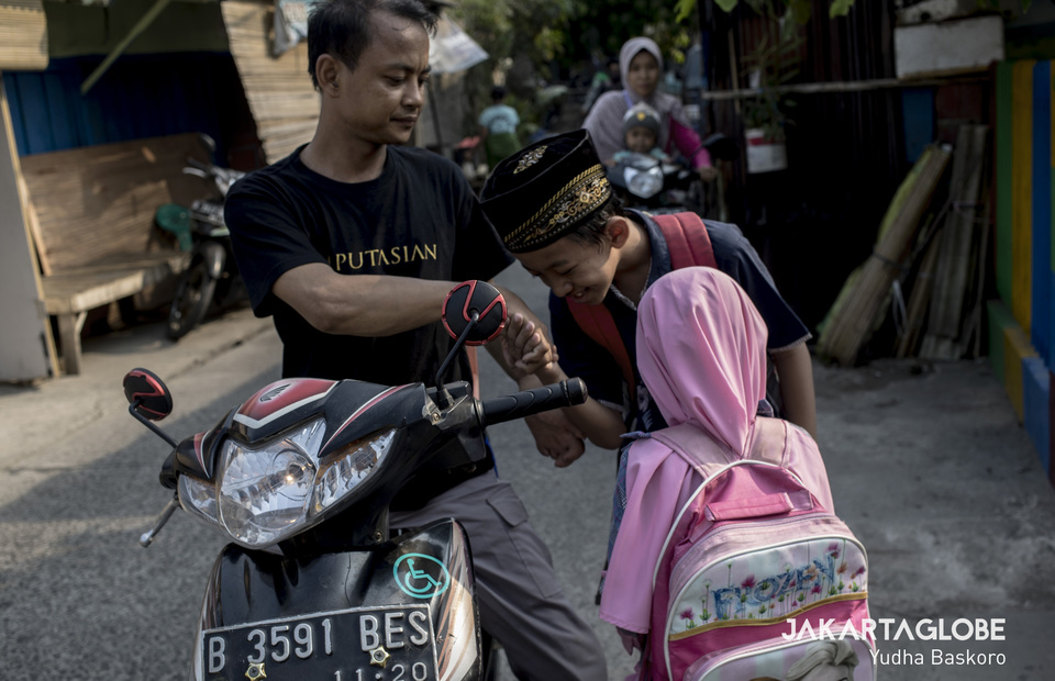 As a father, Oding always rides his non-modified motorcycle to bring his children in a Quran Recitation course near his home in Cengkareng, West Jakarta on Monday (11/11). (JG Photo/Yudha Baskoro)