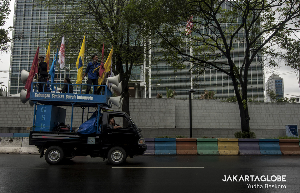 Labour activist march with car commando in front of U.S Embassy, Jakarta on Tuesday (10/12). (JG Photo/Yudha Baskoro)