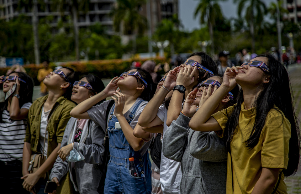 Tourists see the annular solar eclipse using solar glasses in Batam, Riau Islands, Wednesday (26/12). (Antara Photo/M N Kanwa)