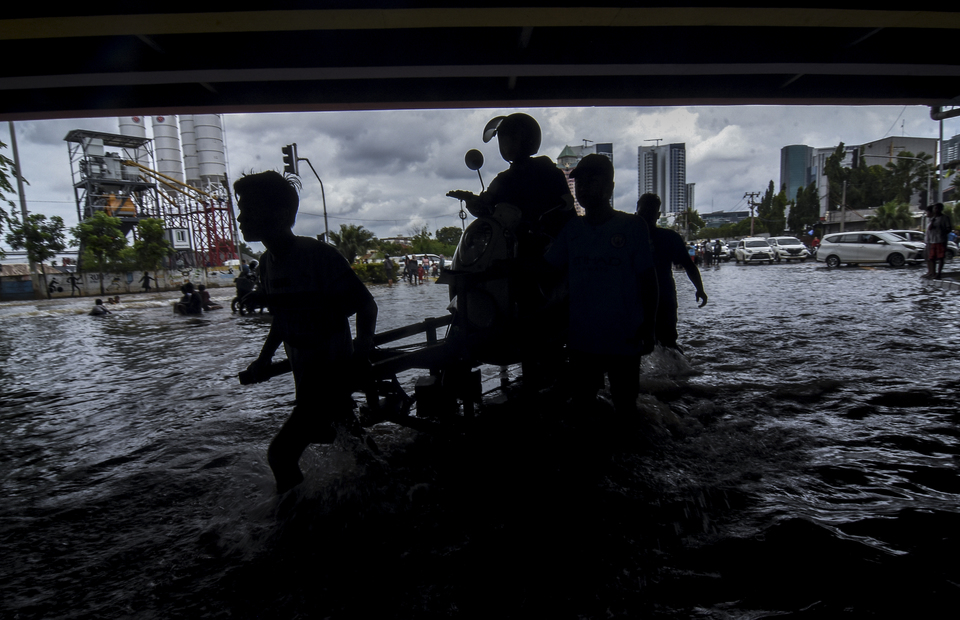 Residents use a cart to transport motorist who wants to cross the flood under the Kembangan flyover, West Jakarta on Thursday (02/01). (Antara Photo/Indrianto Eko Suwarso)