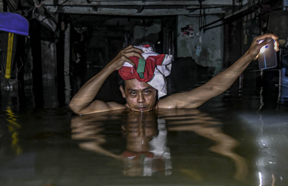 A resident crosses the flood in the Kampung Baru area, Kembangan, West Jakarta, Thursday (02/01). Floods that have occurred since Wednesday are still submerging the area and until now there has been no assistance so that many residents and children are trapped inside their homes. (Antara Photo/Muhammad Adimaja)