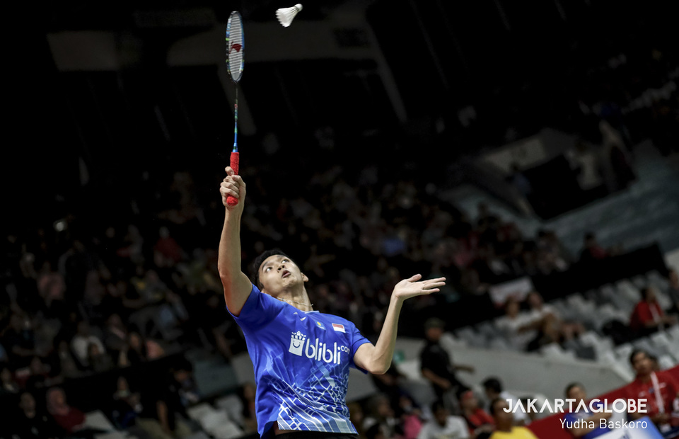 Jonatan Christie jumps for a smash during the men