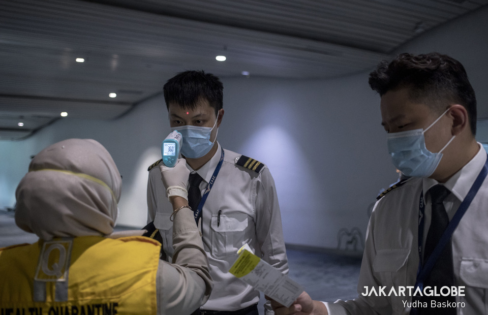 Two pilots who just arrive from Hongkong are inspected by a health inspector at Soekarno-Hatta International Airport on Tuesday (28/01). (JG Photo/Yudha Baskoro)