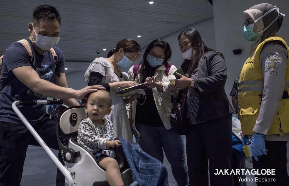 A group of Indonesian peoples explain to passengers from China how to write a yellow card during screening at arrival gate in Soekarno-Hatta International Airport. (JG Photo/Yudha Baskoro)