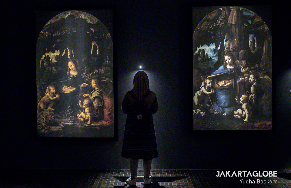 A visitor stands in the middle of two version of Leonardos Virgin of the Rocks painting. (JG Photo/Yudha Baskoro)
