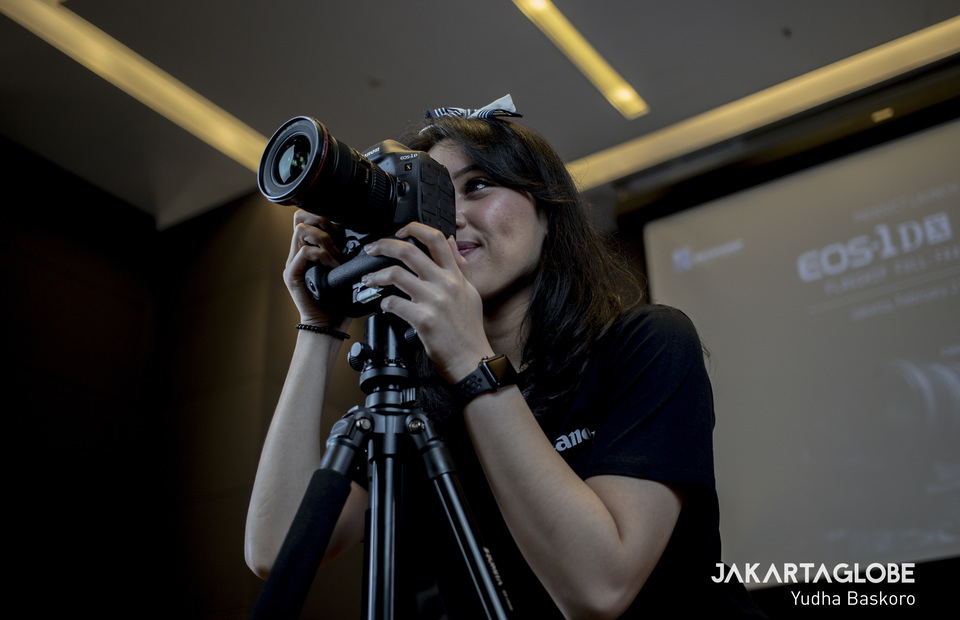 A woman tries the new high-end pro DSLR Canon EOS 1D X Mark III. (JG Photo/Yudha Baskoro)