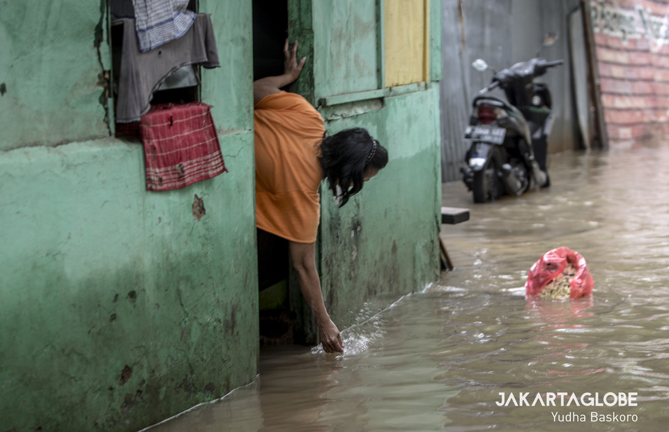 A woman throw a bag of rubbish on the flood. (JG Photo/Yudha Baskoro)