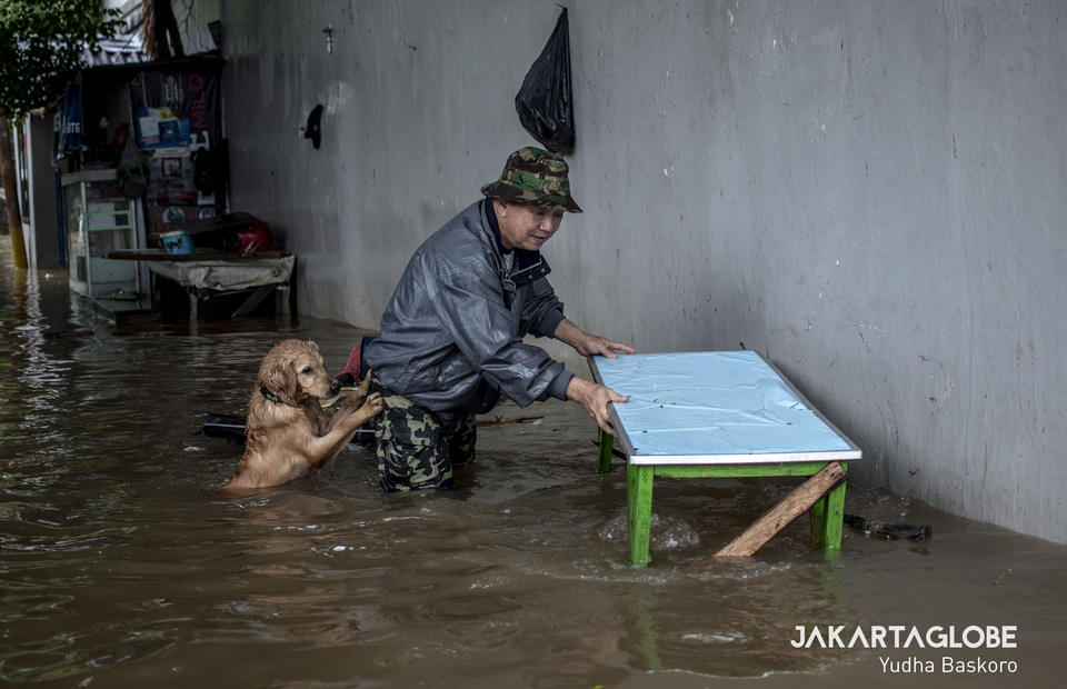 Susanto, 65, brings his dog, Browny to a safe place during flood. (JG Photo/Yudha Baskoro)