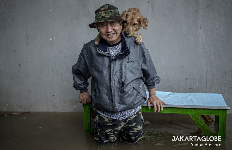 Susanto, 65, stands in flood water while his dog gives him a piggyback during flood in Karet Sawah 2, Setiabudi, South Jakarta on Tuesday (25/02). (JG Photo/Yudha Baskoro)