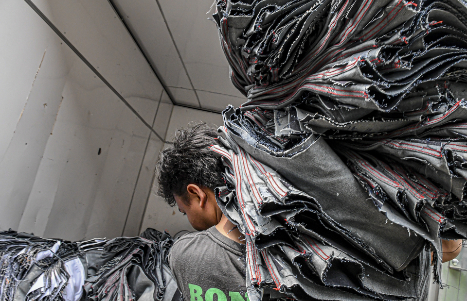 A worker carries a bunch of used clothes