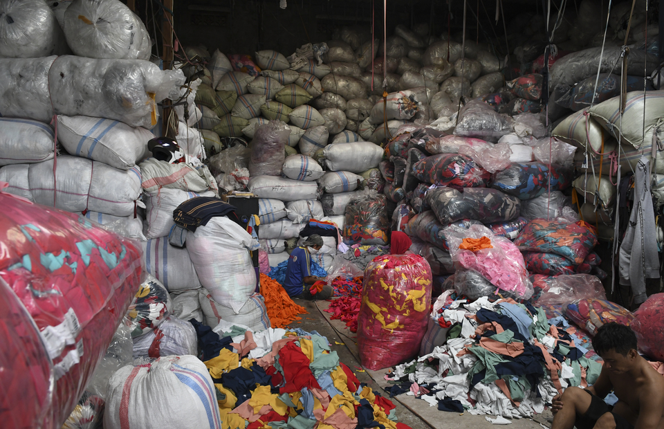 Workers sort out unsold clothes in a fashion waste collectors in Jakarta