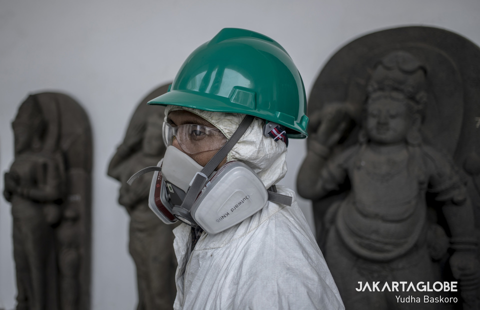 A virus control personnel wearing mask and anti-virus gear as he spreads disinfectant in National Musuem in Central Jakarta on Monday (16/03). (JG Photo/Yudha Baskoro)