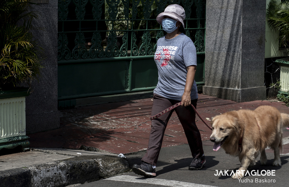 A woman walks with her dog in front of Menteng 01 Elementary School which is temporary closed due to Covid-19 outbreak in Central Jakarta on Friday (20/03). (JG Photo/Yudha Baskoro)