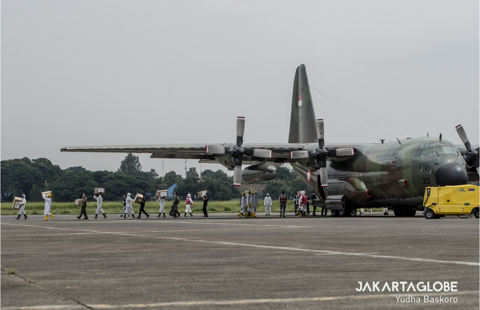 Indonesian Airforce personnels transfer medical equipment from C-130 Hercules aircraft. (JG Photo/Yudha Baskoro)