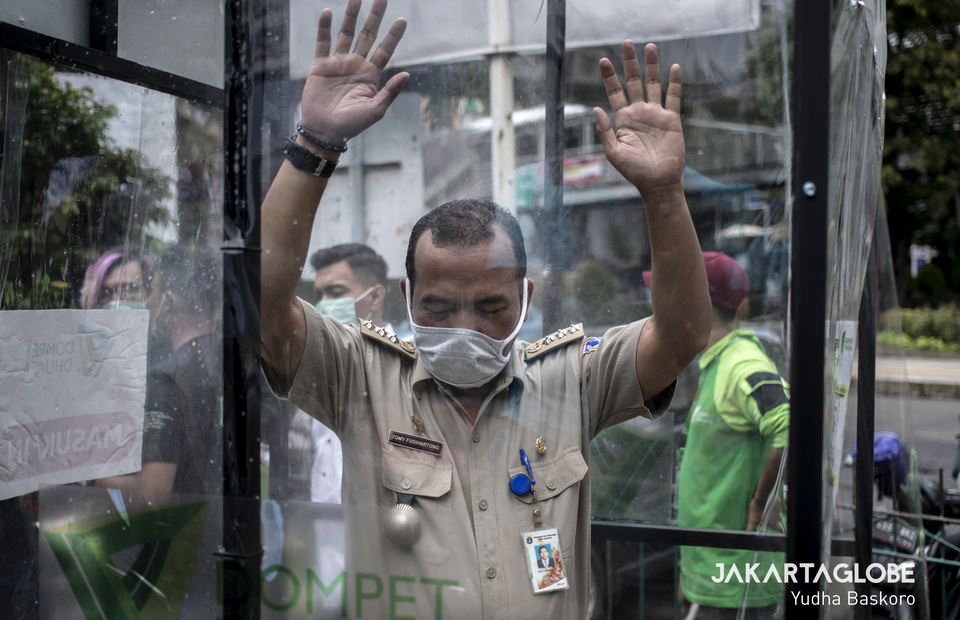 A man tries disinfection chamber as a basic protective measures against the Covid-19 outbreak in front of Blok M Square, South Jakarta on Tuesday (24/03). (JG Photo/Yudha Baskoro)