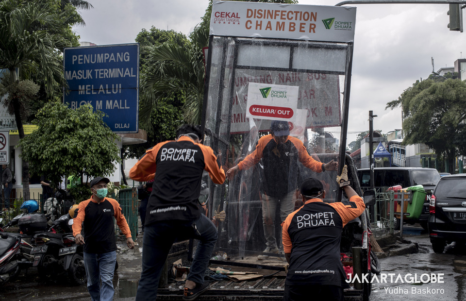 Workers move disinfection chamber from the truck before installed it in front of Blok M Square in South Jakarta on Tuesday (24/03). (JG Photo/Yudha Baskoro)