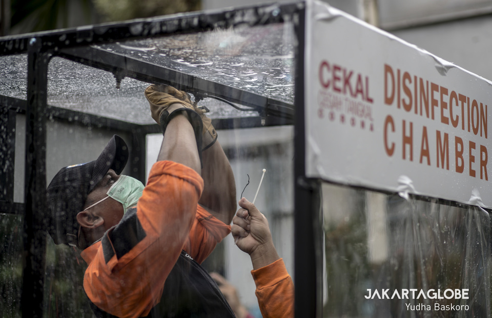 A worker tests a shower inside the disinfection chamber. (JG Photo/Yudha Baskoro)