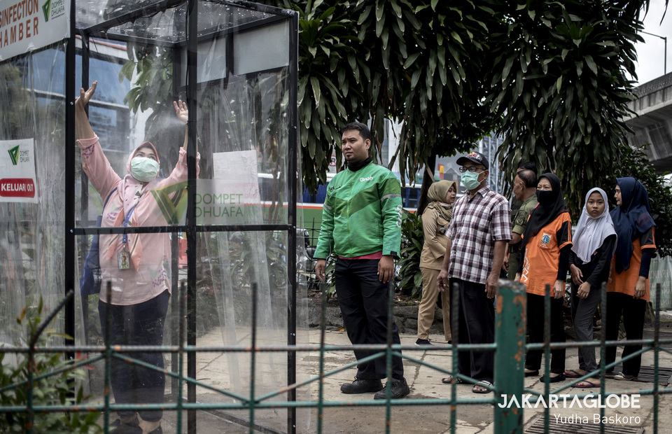 Jakarta residents queue up to try disinfection chamber. (JG Photo/Yudha Baskoro)