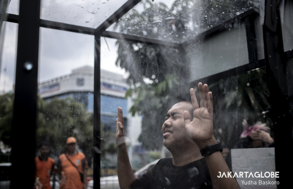 A man enjoying his time inside the disinfection chamber. (JG Photo/Yudha Baskoro)