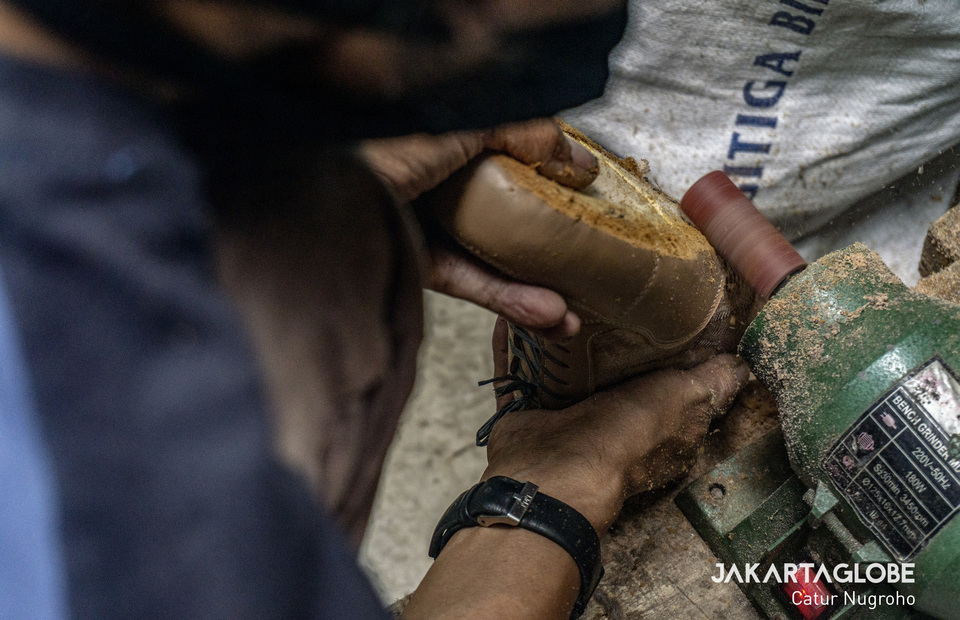 A worker polishes the shoe outsole in Hirka Chicken Foot Shoes industry, Bandung, West Java. (JG Photo/Catur Nugroho)