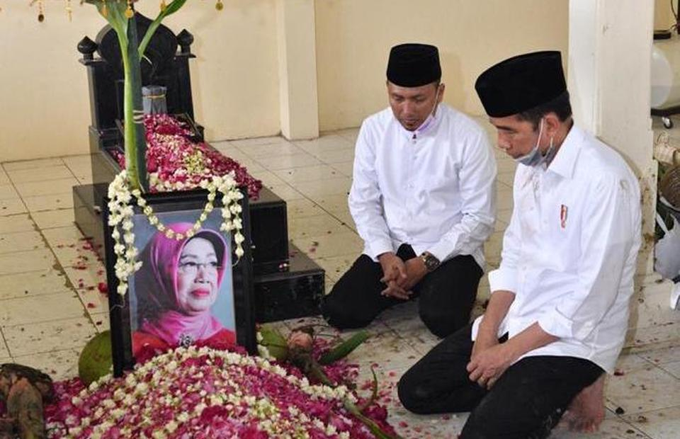 President Joko Widodo, left, pays his last tribute to his late mother Sujiatmi Nitimiharjo at the family