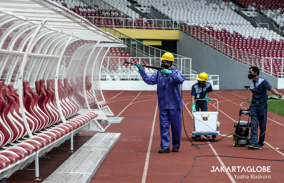 The stadium cleaning service wearing protective gear during disinfection process. (JG Photo/Yudha Baskoro)