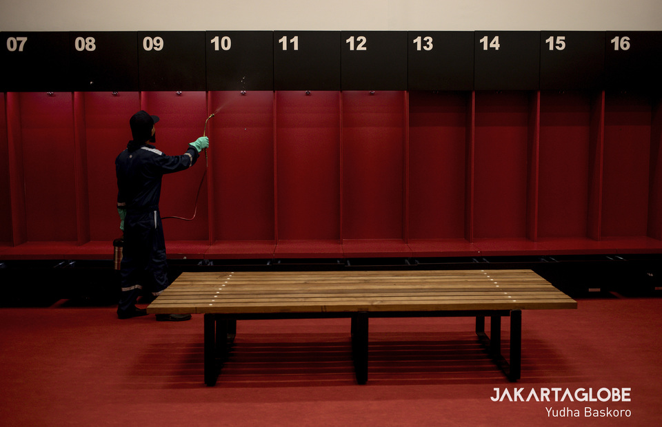 A man sprays a dressing room inside the Gelora Bung Karno Stadium with disinfectant on Thursday (26/03). (JG Photo/Yudha Baskoro)