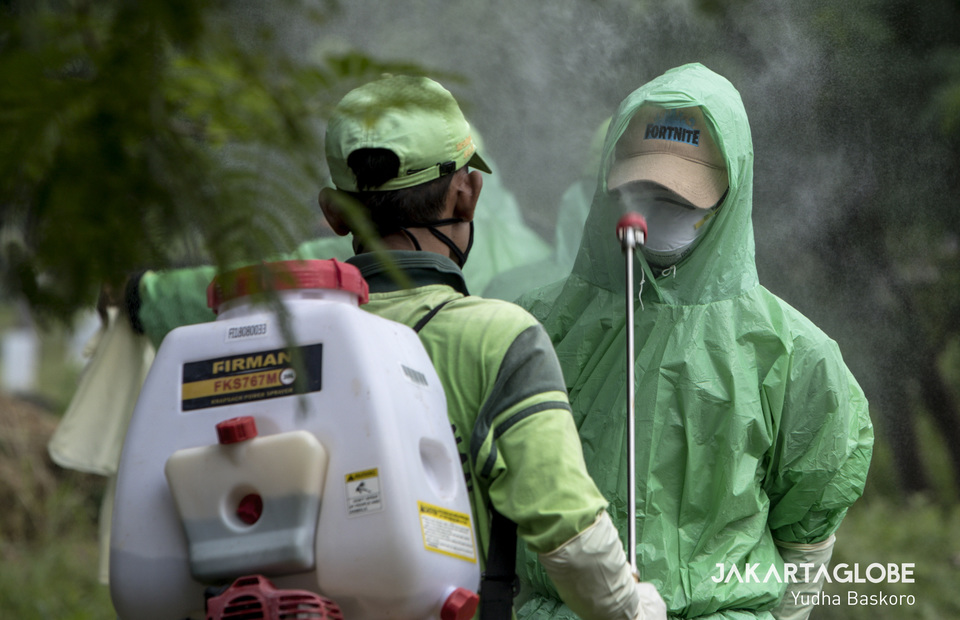 A man sprays a funeral service workers who wearing protective gear with disinfectant. (JG Photo/Yudha Baskoro)