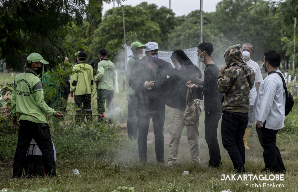 A funeral service worker sprays a family with disinfectant. (JG Photo/Yudha Baskoro)