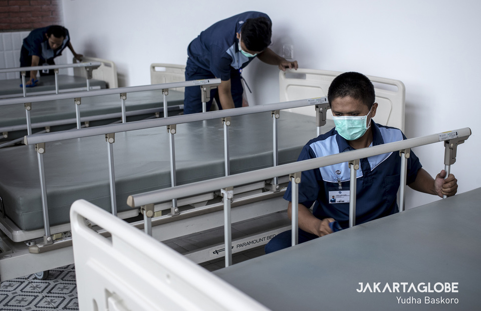 Workers clean bed at makeshift COVID-19 hospital in Lippo Mall Mampang, South Jakarta on Monday (30/03). (JG Photo/Yudha Baskoro)