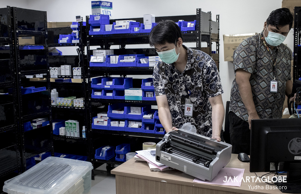 Two medical personnel conduct a routine check inside a medicine stock room at makeshift COVID-19 hospital in Lippo Plaza Mampang, South Jakarta on Monday (30/03) (JG Photo/Yudha Baskoro)