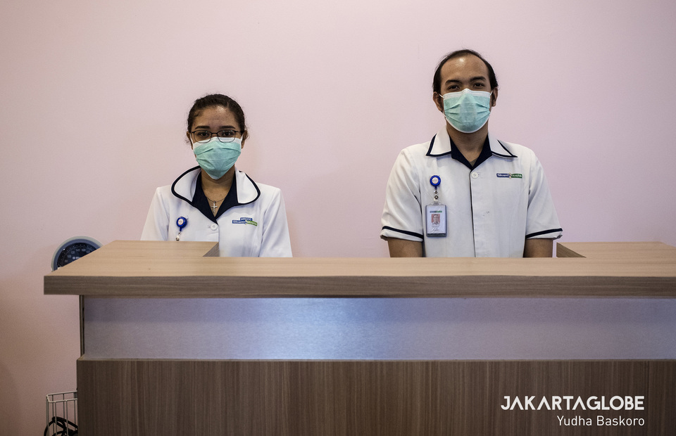 Two medical personnels stand in front of medical treatment room for COVID-19 patients. (JG Photo/Yudha Baskoro)