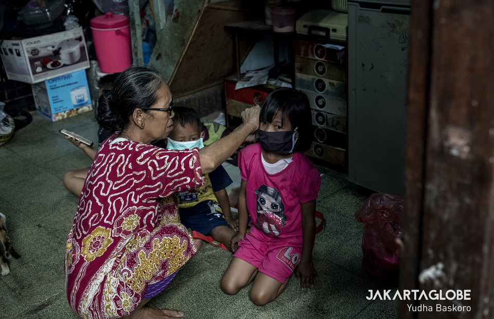 A woman puts a mask on a children in a local lockdown at Tambora, West Jakarta on Wednesday (01/04). (JG Photo/Yudha Baskoro)