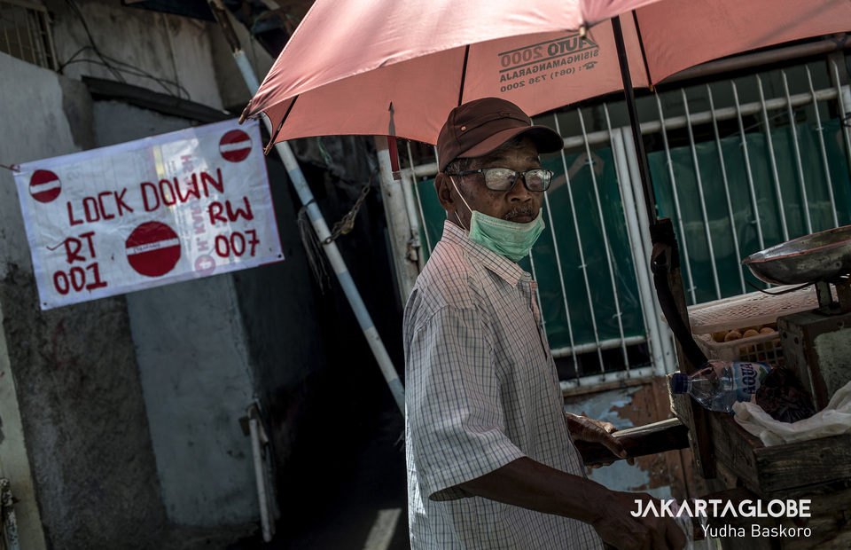 A pedlar walks in front of a small alley which carries out local lockdown in Tambora, West Jakarta on Wednesday (01/04). (JG Photo/Yudha Baskoro)