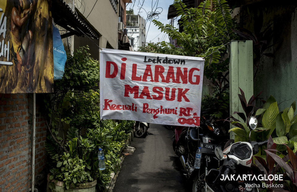 A banner that reads Lockdown, no entry except resident is attached at the small alley in Tambora, West Jakarta on Wednesday (01/04). (JG Photo/Yudha Baskoro)