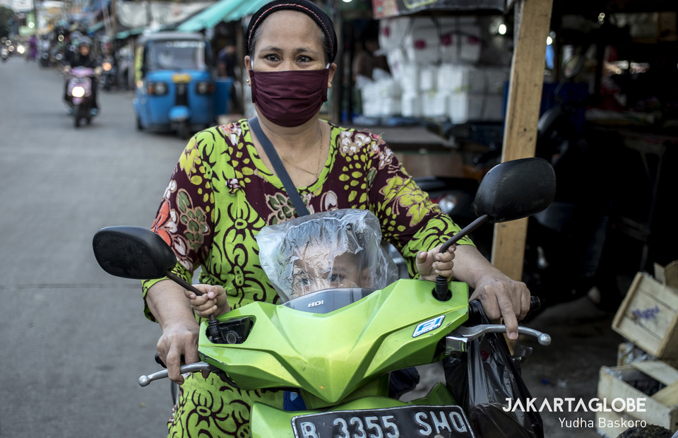 A woman puts on a plastic bag as a mask to her child when she visits Pasar Pintu Air Petamburan in Central Jakarta on Wednesday (01/04). The Government and the Ministry of Trade issued a ban and limitation (Lartas: larangan dan/atau pembatasan) on exports for masks, especially surgical masks and N95. The Government wants to fullfil the needs of masks in the Country during new coronavirus or COVID-19 outbreak. (JG Photo / Yudha Baskoro)