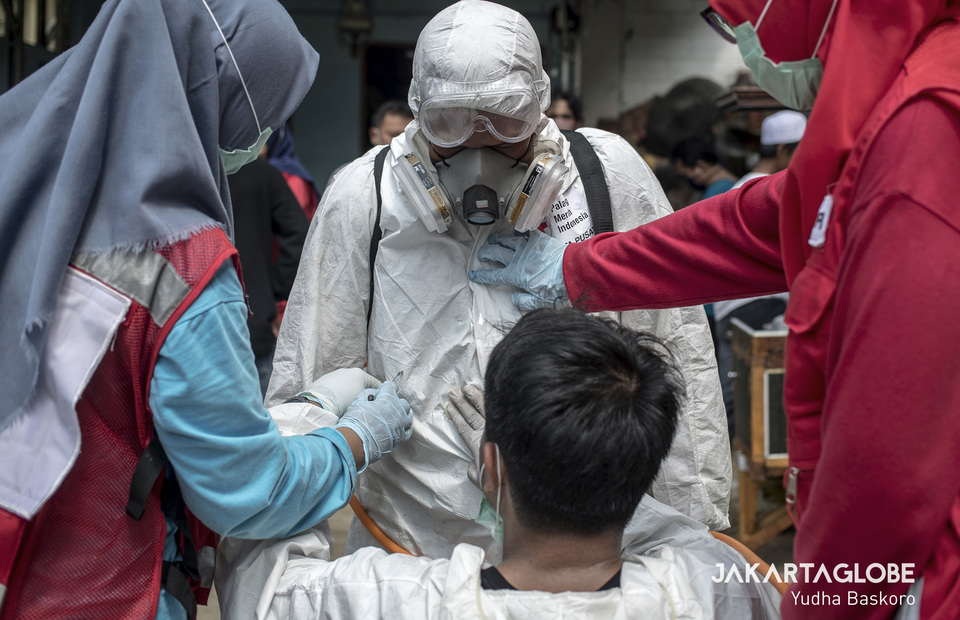 Indonesian Red Cross personnel helping each other to wearing protective gear. (JG Photo/Yudha Baskoro)